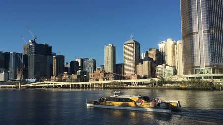 Ferry passing under urban landscape view of Brisbane city downtown skyline and Southbank Parkland in Queensland Australia