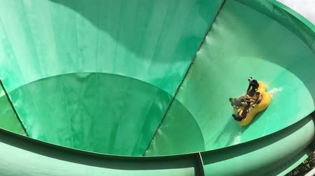 People ride on a water slide named Green Room in White Water World, Gold Coast, Australia