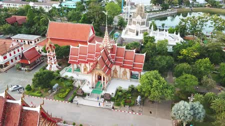 phra : Buddhist church at Chalong temple in Phuket in evening with some people and car moving