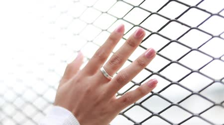 hapis : Woman hand wearing ring touching the metal cage in daytime, Sun light shine thru hole of a cage make soft leak flare Stok Video