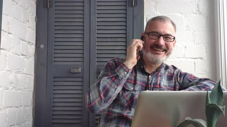 benefício : Gray-haired bearded male accountant making report. He takes a call from the client.