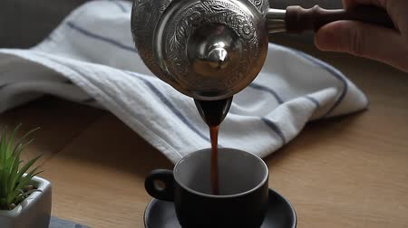 Closeup of male hands pouring coffee from the kettle.
