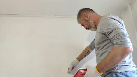 4K Bearded Man Painting interior Walls at Flat using Paint brush. Handsome young man doing Repairs - actively paints wall with white paint. Dostupné videozáznamy