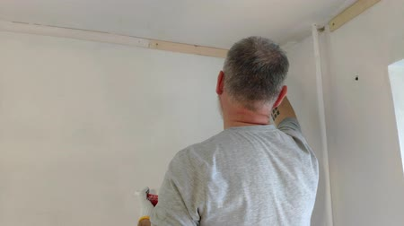 obnova : 4K Bearded Man Painting interior Walls at Flat using Paint brush. Handsome young man doing Repairs - actively paints wall with white paint. Dostupné videozáznamy