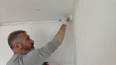riparazioni : 4K Bearded Man Painting interior Walls at Flat using Paint brush. Handsome young man doing Repairs - actively paints wall with white paint. Filmati Stock
