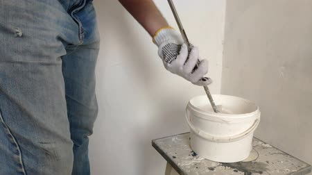 saçlı : A gray-haired bearded man mixes white paint in a bucket by a stick and pours into the container.