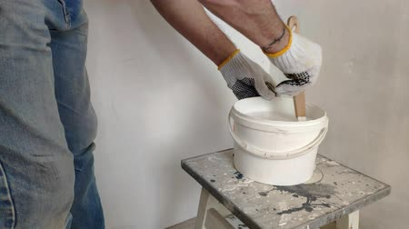 A gray-haired bearded man mixes white paint in a bucket by a stick and pours into the container.