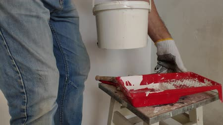javul : A gray-haired bearded man mixes white paint in a bucket by a stick and pours into the container.