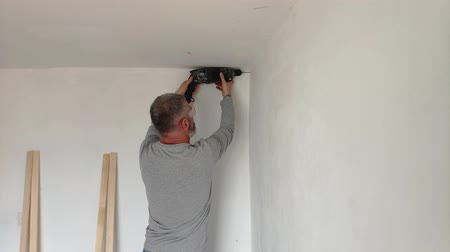 A man drills white wall, drill, concrete, electric drill, Close up hands hold electric drill in white room.