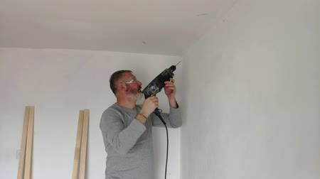 conditioner : A man drills white wall, drill, concrete, electric drill, Close up hands hold electric drill in white room.
