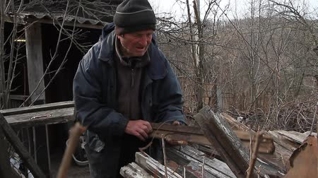 third world : A very old man goes over boards for repairing a hut or kindling fire, life after the war, third world countries, life below the poverty line