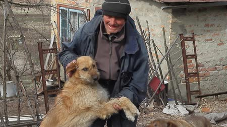 бездомный : A very old man in old poor clothes plays with a big dog that guards his house, life beyond poverty, life in an abandoned village
