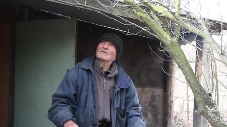 third world : A very old sick man treats garden trees in the spring before flowering from the porch of his house.