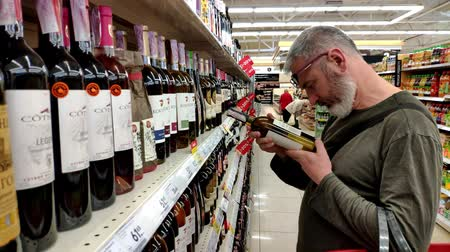 realization : KHARKIV, UKRAINE - April 1, 2019: adult man with a beard chooses wine on a shelf with a glass case in the Ukrainian supermarket, discounts on wine Stock Footage