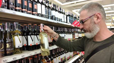 лоза : KHARKIV, UKRAINE - April 1, 2019: adult man with a beard chooses wine on a shelf with a glass case in the Ukrainian supermarket, discounts on wine Стоковые видеозаписи
