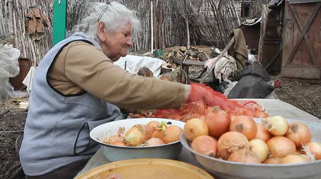 soyulması : An old woman with gray hair picks up onions before cooking in the kitchen, organic vegetables, her own crop, selective focus Stok Video
