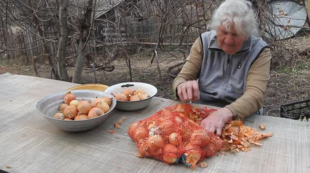 kendi : An old woman with gray hair picks up onions before cooking in the kitchen, organic vegetables, her own crop, selective focus Stok Video