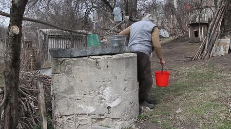 bezdomny : An old woman in a deserted village is gathering water from a well in a bucket, living alone.