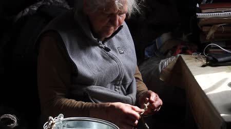 собственность : Old woman with sore hands knits knots on a rope to lower a bucket into a well, life in an abandoned village, selective focus