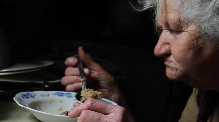 doar : An old woman with gray hair is eating a bag from a plate in her old dilapidated house, life in an abandoned village, selective focus