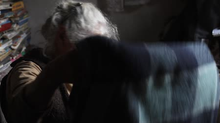 doar : An old woman with gray hair sorts through old things, cleans the bed in her old house, living alone, selective focus