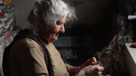 bezdomny : An old woman with gray hair sorts through old things, cleans the bed in her old house, living alone, selective focus