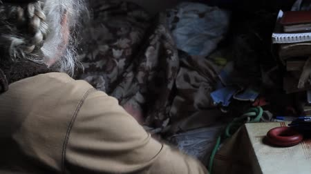 alku : An old woman with gray hair sorts through old things, cleans the bed in her old house, living alone, selective focus
