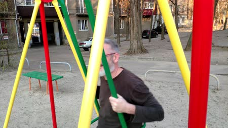 özlem : Gray-haired bearded man riding on a swing, rejoices and smiles, concept of a happy childhood.