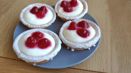 fondán : Closeup of four pannacots with raspberries on a gray plate on a light wooden table.