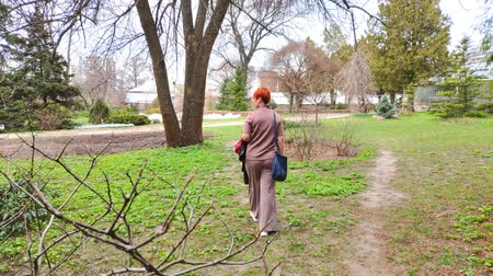 pedestrian only : Rear view of a young adult woman with a short red haircut walks through the botanical garden in spring. Stock Footage