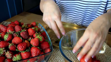 clear the table : Close up of female hands peel fresh large strawberries for later use