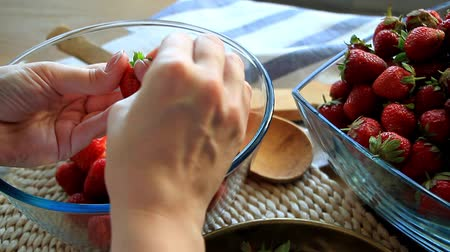 útil : Close up of female hands peel fresh large strawberries for later use