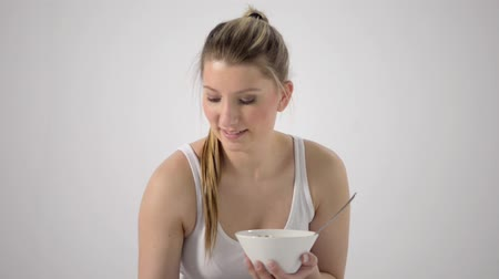 sürahi : Young sexy girl is sitting in a white room, pours milk in a cup with cereals and eats it