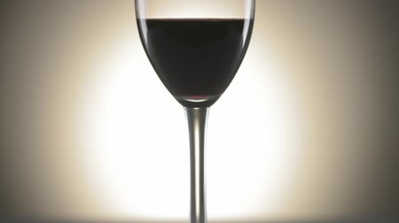 close up shot : Medium shot of a wine glass with redwine and a bright spot in background, tilt from bottom to top Stock Footage
