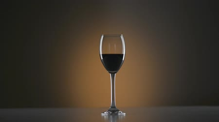 kırmızı şarap : Wide shot of a wine glass with redwine and a bright spot in background fading up and down