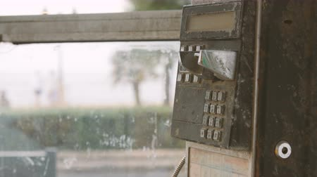 telecoms : Old black rusty phone in phone booth coin. A womans hand picks a Handset. Stock Footage