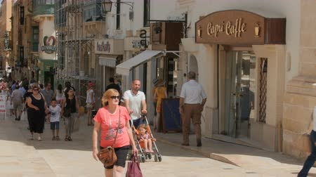 maltština : MALTA CAPITAL VALLETTA CITY CENTRE, PEDESTRIAN STREET - JULY 2016: Many tourist and local people shopping in the old downtown full of shops, cafe, pharmacy kids playing, friends chatting. Dostupné videozáznamy