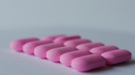 dragee : Pink medication pill turning on a table on a white background. Stock Footage