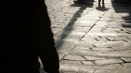 parke taşı : Silhouettes of people on the cobblestone pavement, evening. Stok Video