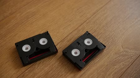 videocassette : Mini DV cassettes falling on the floor, slow motion.