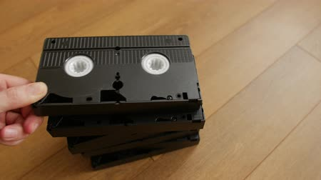 videocassette : Stack of VHS video tape cassette over wooden background, top view, close up.