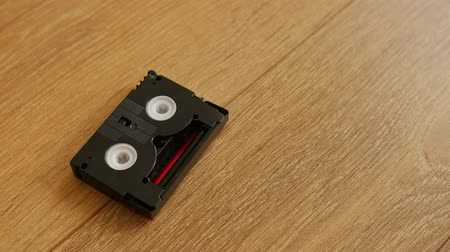 videocassette : Mini DV cassettes falling on the floor, close up. Stock Footage