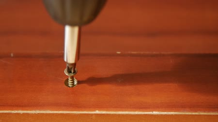 cabinetry : Close up of a wood screw being drilled into a board, slow motion.