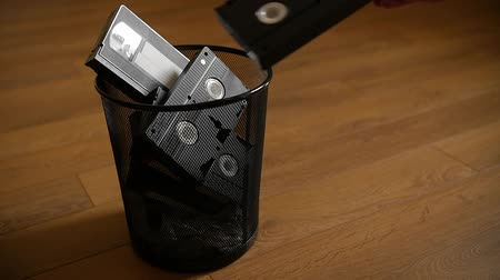 videocassette : A bunch of cassettes thrown in the trash over wooden background. Slow motion.