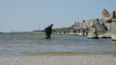 semi precious : Klaipeda, Lithuania. Man near the breakwater,searching valuable amber in sea.