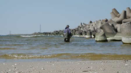 klaipeda : Klaipeda, Lithuania. Man near the breakwater,searching valuable amber in sea.