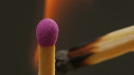 streaking : Match lighting another one, sharing fire, burning stick close up. Black background. Stock Footage