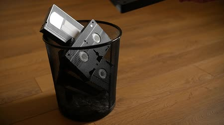 casette : A bunch of cassettes thrown in the trash over wooden background. Slow motion.