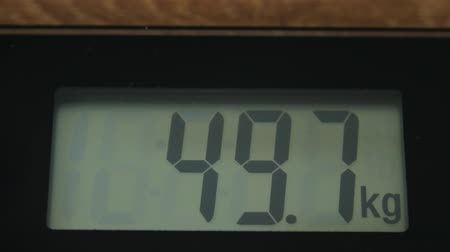 weighing machine : Bathroom digital scale close up with digits running up.