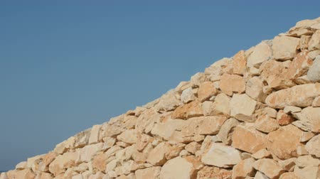 brickwall : A fragment of a yellow stone wall on a blue sky background. Stock Footage
